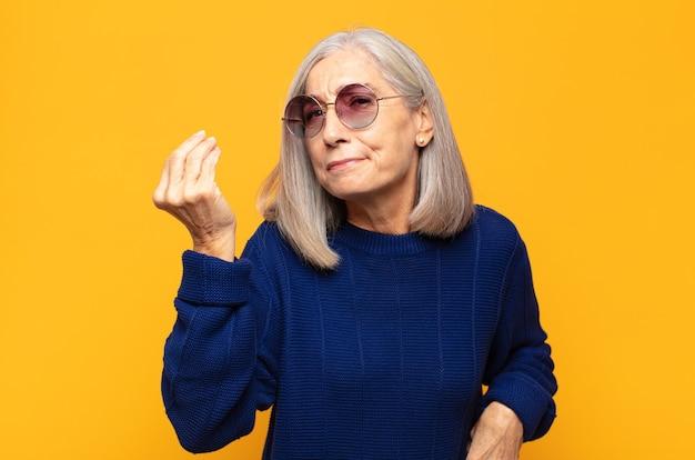Mulher de meia idade fazendo capice ou gesto de dinheiro, mandando você pagar suas dívidas!