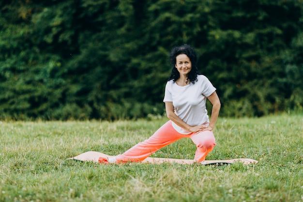 Mulher de meia idade fazendo exercício ao ar livre e esticando as pernas dela. esporte