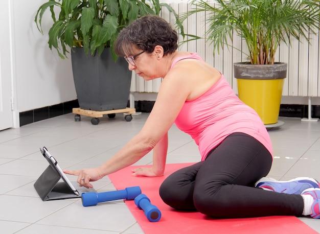 Mulher de meia idade fazendo exercícios de fitness com tablet