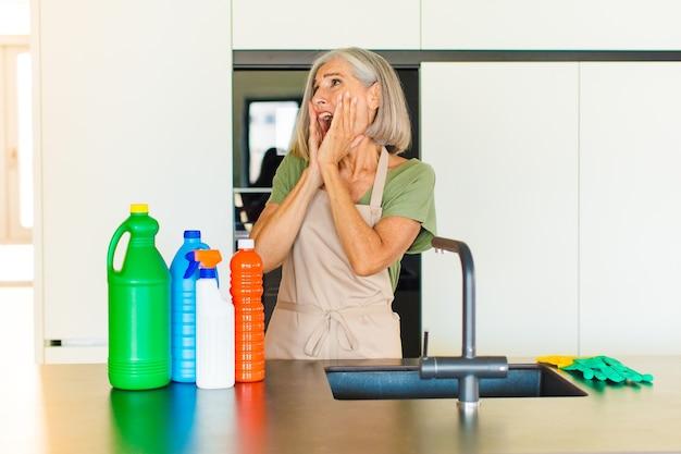 Mulher de meia-idade feliz, animada e surpresa, olhando para o lado com as duas mãos no rosto