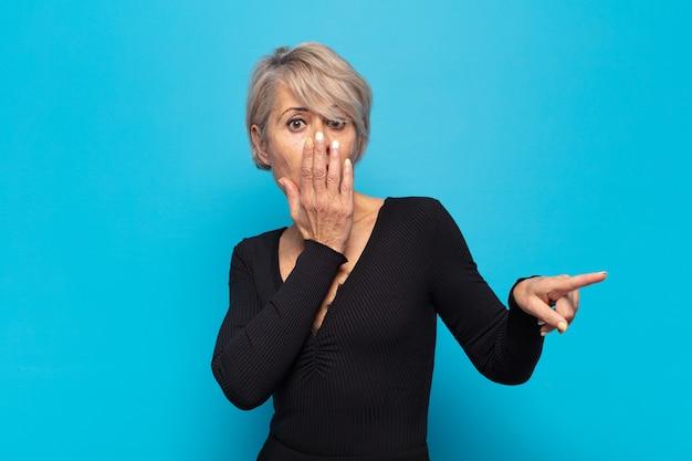 Mulher de meia-idade feliz, chocada e surpresa, cobrindo a boca com a mão e apontando para o espaço lateral da cópia
