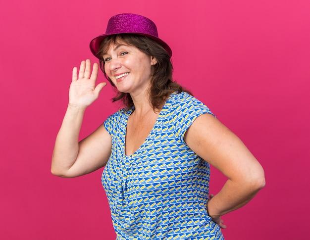 Mulher de meia-idade feliz com chapéu de festa sorrindo alegremente, acenando com a mão e comemorando a festa de aniversário em pé sobre a parede rosa