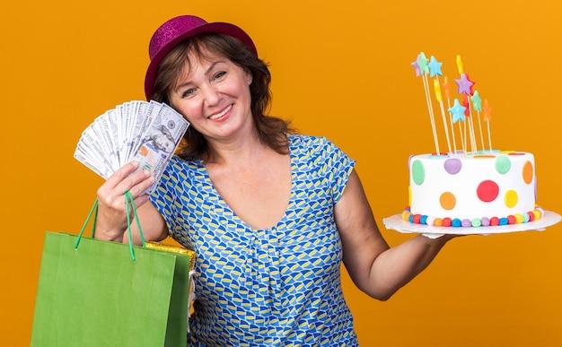 Mulher de meia-idade feliz com um chapéu de festa segurando um saco de papel com presentes segurando um bolo de aniversário e dinheiro sorrindo amplamente