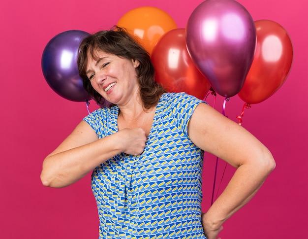 Mulher de meia-idade feliz e alegre com chapéu de festa e balões coloridos sorrindo amplamente