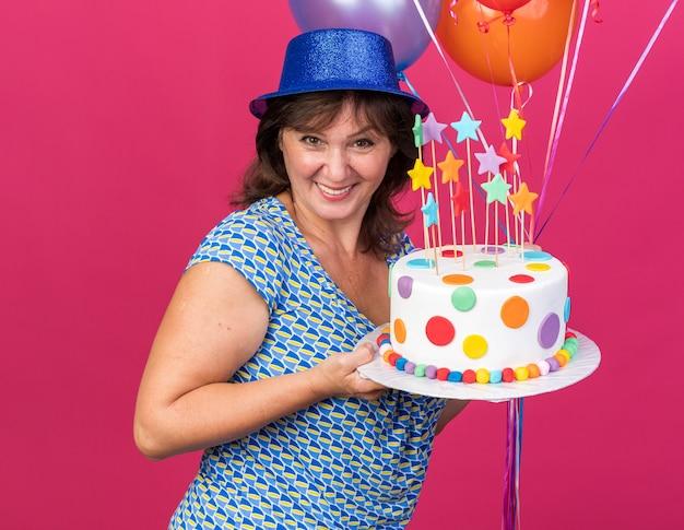 Mulher de meia-idade feliz e alegre com um chapéu de festa com balões coloridos segurando um bolo de aniversário com um sorriso largo