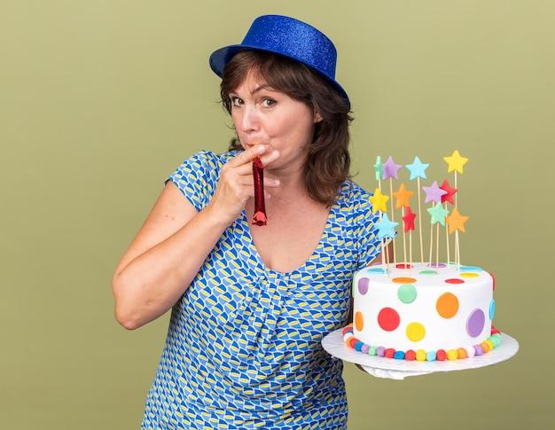 Mulher de meia-idade feliz e alegre com um chapéu de festa segurando um bolo de aniversário, soprando um apito