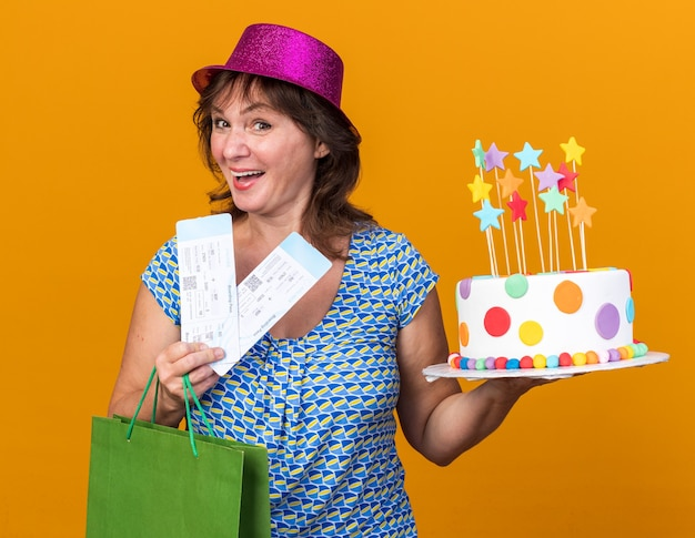 Mulher de meia-idade feliz e alegre com um chapéu de festa segurando um saco de papel com presentes segurando um bolo de aniversário e passagens aéreas