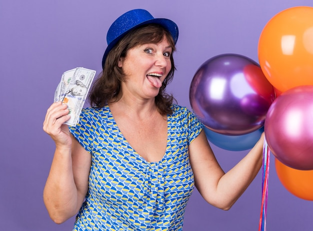 Mulher de meia-idade feliz e animada com um chapéu de festa com um monte de balões coloridos segurando dinheiro e mostrando a língua