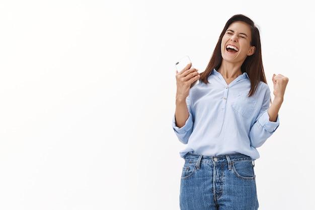 Mulher de meia-idade, feliz e animada, mulher de meia-idade, vencedora de uma viagem de férias excelente, receba uma excelente mensagem de texto, segure o smartphone dançando, sacuda o punho exultando o sucesso, sorrindo amplamente, parede branca