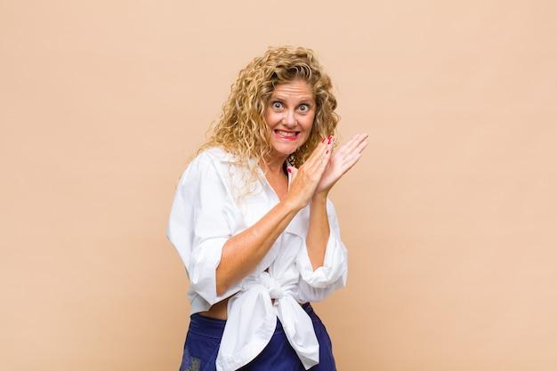 Mulher de meia-idade feliz e bem-sucedida, sorrindo e batendo palmas, parabenizando-se e aplaudindo