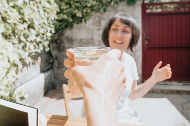 Mulher de meia-idade feliz e sorridente tomando um drink em um dia super ensolarado