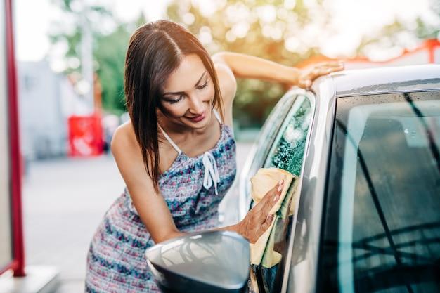 Mulher de meia-idade feliz lavando carro à noite na estação de lavagem de carros.