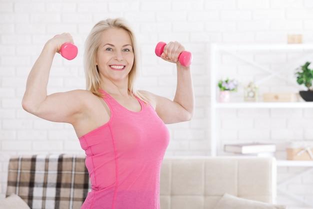 Mulher de meia-idade feliz levantando halteres em casa na sala de estar