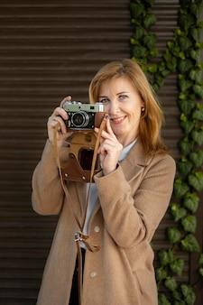 Mulher de meia idade feliz segurando uma câmera