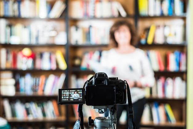 Mulher de meia idade gravando uma aula online com sua câmera de vídeo
