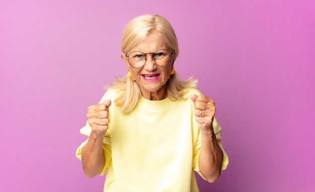 Mulher de meia idade gritando agressivamente com olhar irritado, frustrado e irritado e punhos cerrados, sentindo-se furiosa