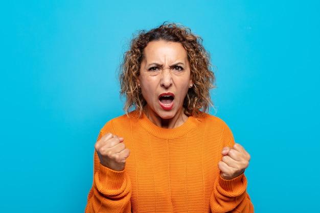 Mulher de meia-idade gritando agressivamente com olhar irritado, frustrado e raivoso e punhos cerrados, sentindo-se furiosa
