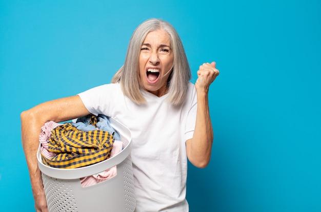 Mulher de meia-idade gritando agressivamente com uma expressão de raiva ou com os punhos cerrados celebrando o sucesso