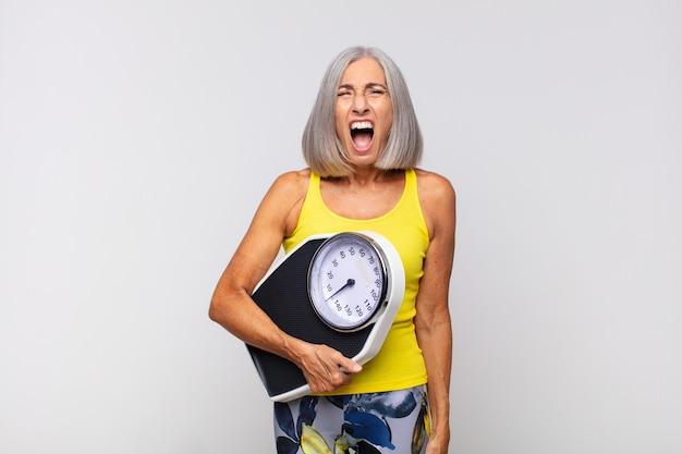 Mulher de meia idade gritando agressivamente, parecendo muito zangada