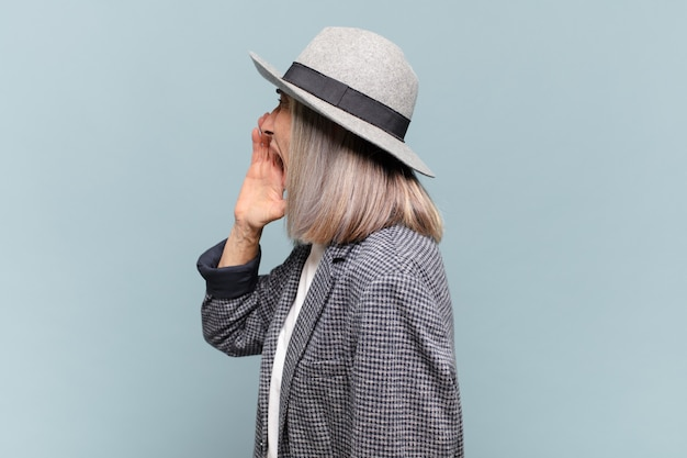 Mulher de meia-idade gritando alto e com raiva para copiar o espaço ao lado, com a mão perto da boca