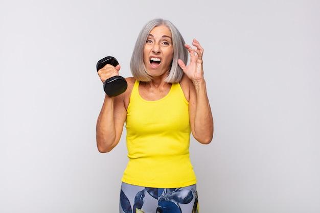 Mulher de meia-idade gritando com as mãos ao alto, furiosa