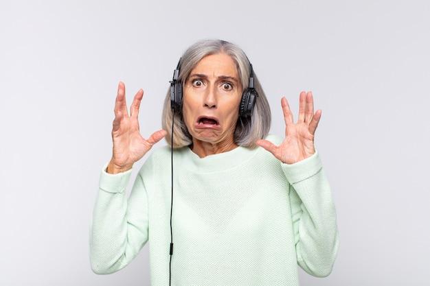 Mulher de meia idade gritando com as mãos ao alto, sentindo-se furiosa, frustrada, estressada e chateada. conceito de musica