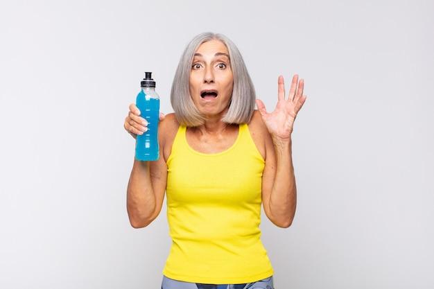 Mulher de meia-idade gritando com as mãos ao alto, sentindo-se furiosa, frustrada, estressada e chateada