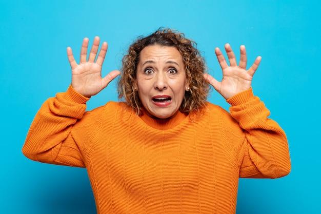 Mulher de meia-idade gritando em pânico ou raiva, chocada, apavorada ou furiosa, com as mãos perto da cabeça