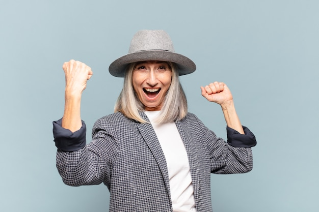 Mulher de meia-idade gritando triunfantemente, parecendo uma vencedora animada, feliz e surpresa, comemorando