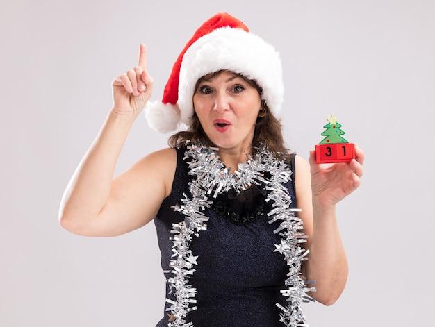 Mulher de meia-idade impressionada com chapéu de papai noel e guirlanda de ouropel no pescoço segurando um brinquedo de árvore de natal com data olhando para a câmera apontando para cima, isolado no fundo branco