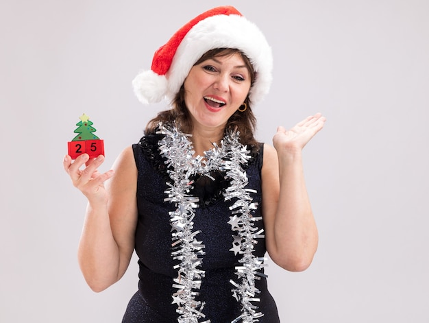 Mulher de meia-idade impressionada com chapéu de papai noel e guirlanda de ouropel no pescoço segurando um brinquedo de árvore de natal com data olhando para a câmera mostrando a mão vazia isolada no fundo branco com espaço de cópia