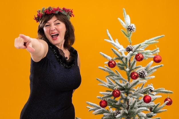 Mulher de meia-idade impressionada com uma coroa de natal na cabeça e uma guirlanda de ouropel em volta do pescoço, perto de uma árvore de natal decorada