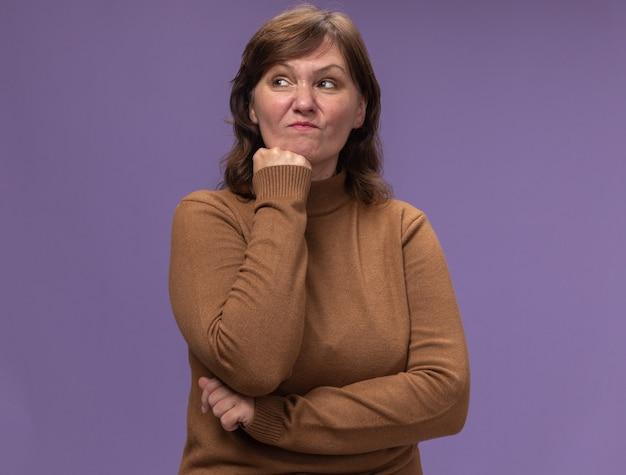 Mulher de meia-idade insatisfeita com gola olímpica marrom olhando para o lado com a mão no queixo pensando em pé sobre uma parede roxa