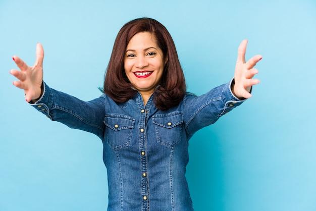 Mulher de meia idade latina isolada no azul se sente confiante dando um abraço
