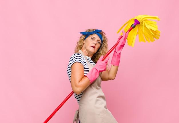 Mulher de meia-idade legal com um esfregão na parede rosa