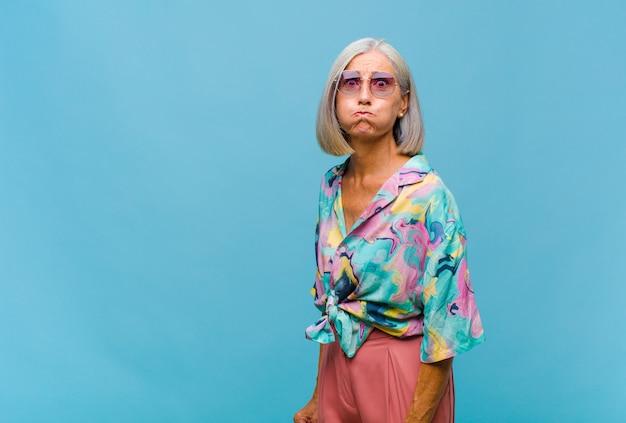 Mulher de meia-idade legal com uma expressão boba, louca e surpresa, bochechas estufadas, se sentindo recheada, gorda e cheia de comida