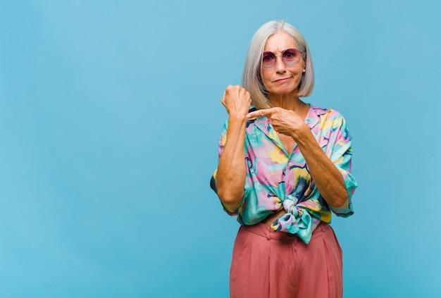 Mulher de meia-idade legal, impaciente e zangada, apontando para o relógio, pedindo pontualidade, quer ser pontual