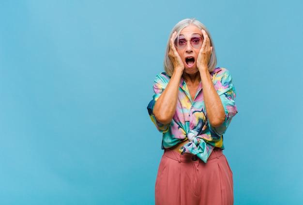 Mulher de meia-idade legal parecendo desagradavelmente chocada, assustada ou preocupada, boca bem aberta e cobrindo as orelhas com as mãos
