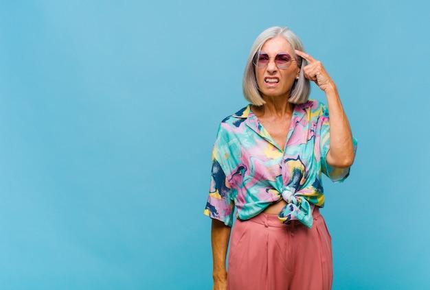 Mulher de meia-idade legal se sentindo confusa e intrigada, mostrando que você é louco, louco ou louco