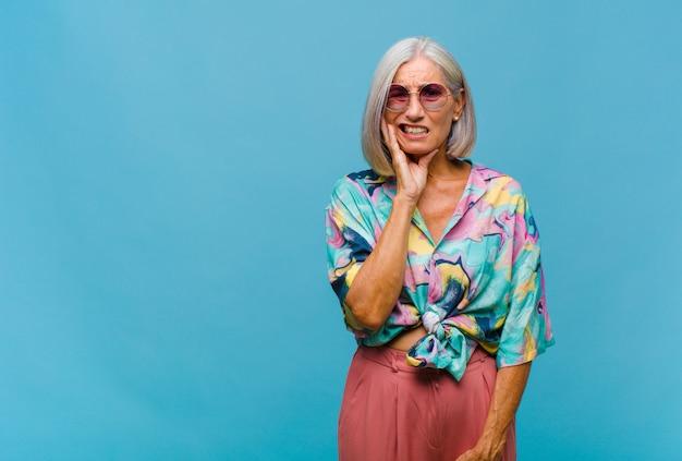 Mulher de meia-idade legal segurando a bochecha e sofrendo de uma dor de dente dolorida, sentindo-se doente, miserável e infeliz