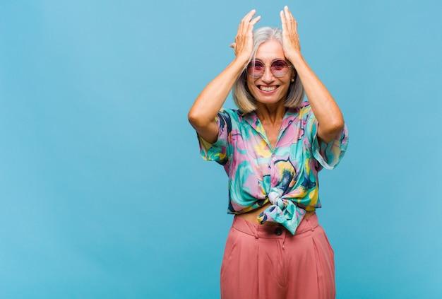 Mulher de meia-idade legal sentindo-se estressada e ansiosa, deprimida e frustrada com uma dor de cabeça, levando as duas mãos à cabeça