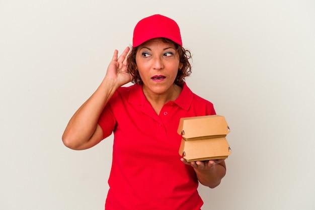 Mulher de meia idade levando hambúrgueres isolados no fundo branco, tentando ouvir uma fofoca.