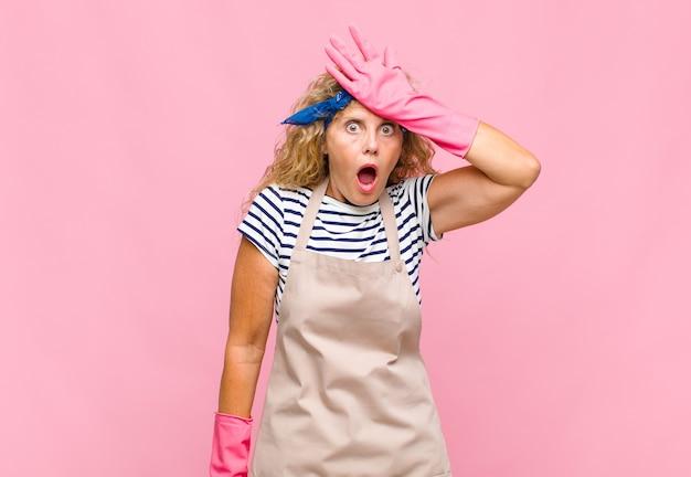 Mulher de meia-idade levantando a palma da mão na testa pensando opa, depois de cometer um erro estúpido ou lembrar, sentindo-se burra