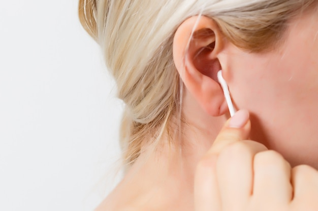 Mulher de meia-idade, limpando a orelha com cotonete ou bastão. close do procedimento de rotina de higiene e saúde em casa