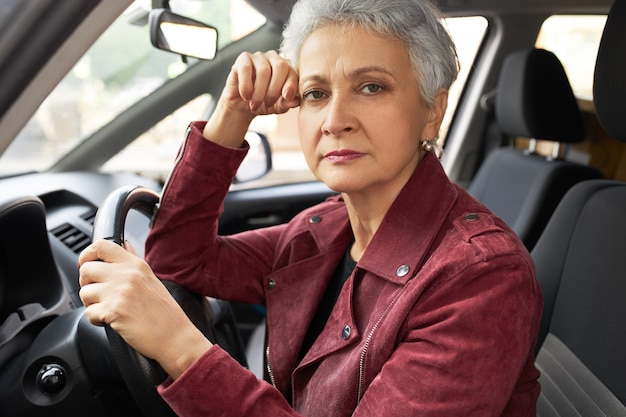 Mulher de meia-idade moderna bem-sucedida em roupas elegantes, com rosto facial perturbado dentro do carro