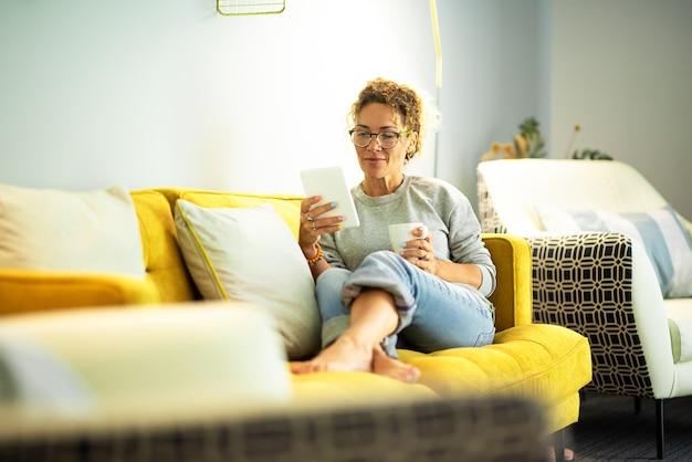 Mulher de meia-idade moderna lê um e-book em um tablet, sentada confortável no sofá em casa, aproveitando o tempo de lazer dentro de casa sozinha - senhora caucasiana estudando em dispositivo digital - aula on-line com pessoas