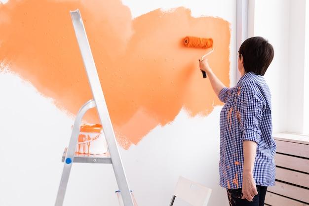 Mulher de meia-idade muito sorridente, pintando a parede interior da casa com rolo de pintura.