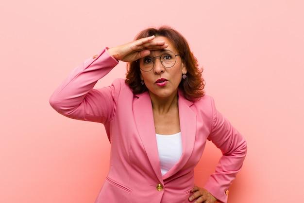 Mulher de meia idade, olhando confusa e atônita, com a mão na testa, olhando para longe, assistindo ou pesquisando na parede rosa