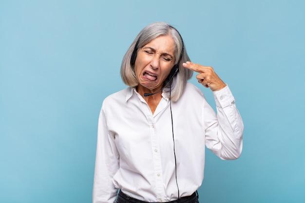 Mulher de meia-idade olhando infeliz e estressada, gesto de suicídio fazendo sinal de arma com a mão, apontando para a cabeça. conceito de telemarketing