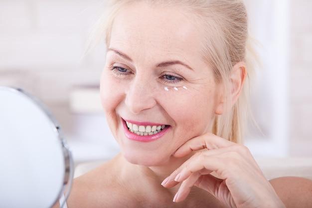 Mulher de meia idade olhando para as rugas no espelho. foco seletivo